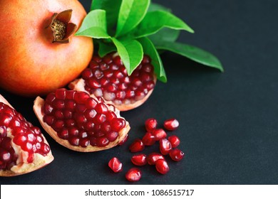 Sweet and juicy Indian pomegranate on black granite table in top view with copy space for background or wallpaper. Healthy and delicious fruit which have high vitamin c and antioxidant for good skin.