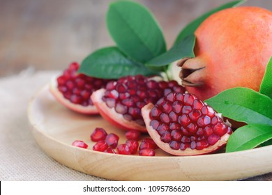 Sweet and juicy Indian red pomegranate on wooden plate on wood table with copy space for background or wallpaper. Delicious and healthy fruit which have high vitamin c and antioxidant for good skin.