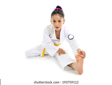 sweet latin little girl alone stretching leg in martial arts practice like karate kid  isolated on white background