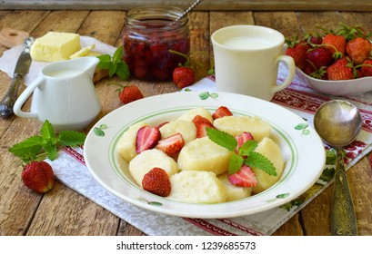 Sweet lazy pierogi. Ukrainian dumplings with sour cream, butter and strawberry on wooden background. Summer berry breakfast. Italian gnocchi. Copy space