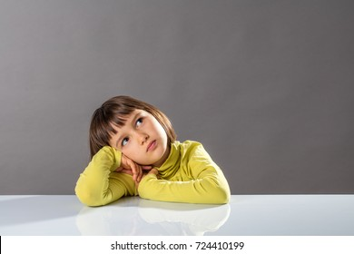 sweet little 6-year old pouting thinker leaning her head on her desk, looking away for concept of kid boredom, imagination, curiosity, doubt and intelligence, grey background, copy space