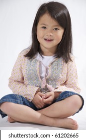 Sweet little Asian Girl sitting on a white background