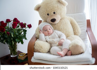 Sweet little baby boy, sleeping with huge teddy bear in big armchair, littlr table with vase with roses flowers next to him