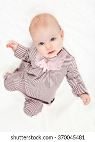 Sweet little baby girl in striped pink costume laying on white background. Top view.