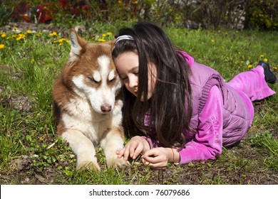 Sweet little baby husky on the grass with her little owner