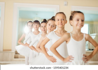 sweet little ballerinas in white tutu skirts stand in a row, group dance of classic ballet in studio, ballet school