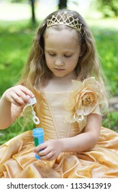 A sweet little blonde girl, in a golden crown and golden dress with soap babbles