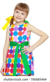 A sweet little blonde girl with long pigtails, in which large colored bows are braided, and a short bangs on her head. In a short summer dress.She gestures.