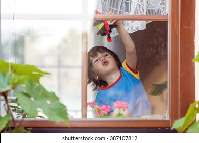 Sweet little boy, playing with airplane early in the morning on the window, view from outdoor through the window