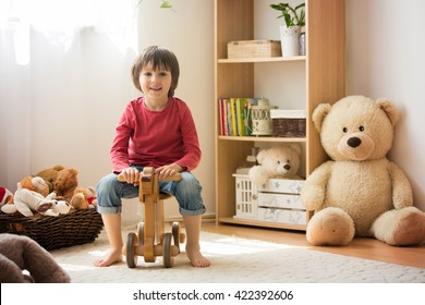 Sweet little boy, preschool child, playing at home with wooden horse, childhood games