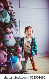 sweet little boy standing near green Christmas tree