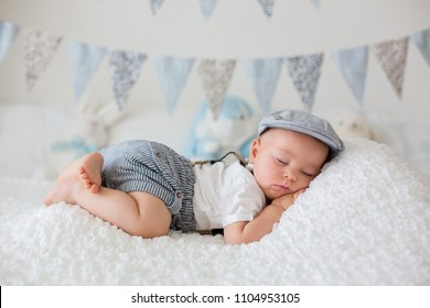 Sweet little child, baby boy, sleeping in a sunny bedroom during the day, having a rest, flag banner decoration on the wall behind him