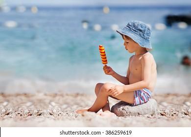 Sweet little child, boy, eating ice cream on the beach, summertime
