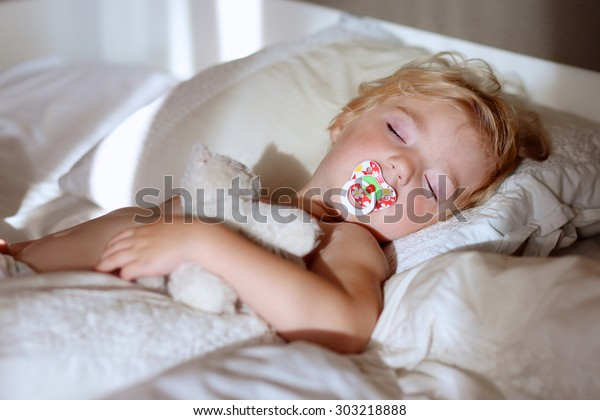 Sweet little child sleeping cozy in bed. Healthy kid, blonde toddler girl, resting in bed in white sunny bedroom.