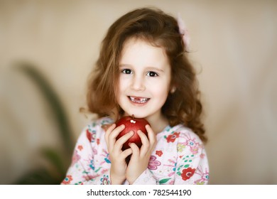 A sweet little curly tooth with brown eyes the girl smiles and holds in her hands a red apple that has lost milk teeth