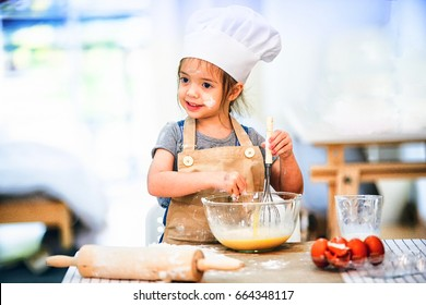 Sweet little cute girl is learning how to make a cake, in the home kitchen, Family concept, Vintage color tone.