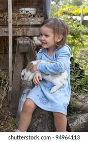 Sweet little girl 3 years old hugs her baby rabbit in the farm yard