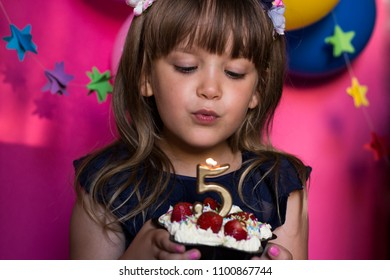 Sweet little girl celebrating her birthday and blowing cande on her homemade strawberry cake. Make a wish concept. Anniversary, happiness. Five years old. Selectiv focus