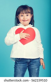 Sweet little girl with Down Syndrome, playing with paper heart