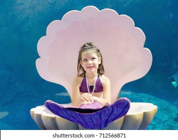Sweet little girl dressed in mermaid costume stay thinking in big shell on blue aquarium background