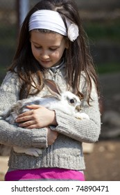Sweet little girl in a farmyard with baby animals