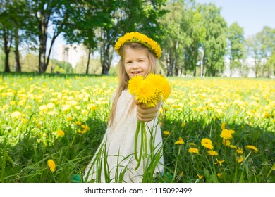 Sweet little girl with floral head wreath on and flowers bunch in hands in summer park