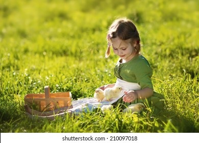 A sweet little girl in a green dress sitting with chicks on the bright grass in a sunny summer day. Kids and nature