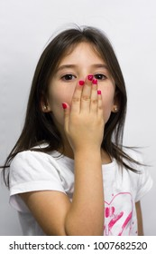Sweet little girl with hand on mouth about to send a kiss over white background. Pink polish nails