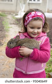 Sweet little girl hold a rabbit in the farm.
