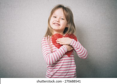 sweet little girl holds a valentines heart and thinks of love, isolated on gray background