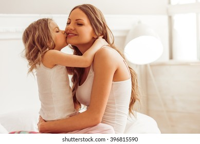 Sweet little girl is hugging and kissing her beautiful young mom in cheek while sitting on bed at home