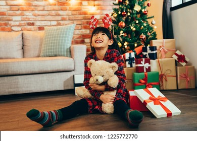 Sweet little girl hugging teddy bear looking up to sky smiling sitting on wooden floor. attractive childhood received gift on Christmas sale at home. kid with reindeer satisfied with present.