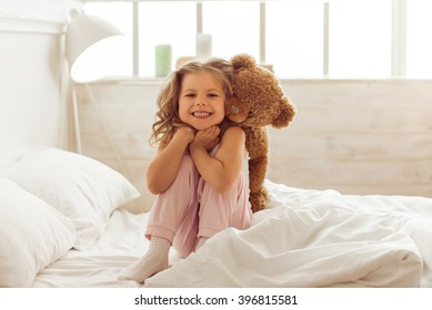 Sweet little girl is hugging a teddy bear, looking at camera and smiling while sitting on her bed at home