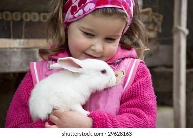 Sweet little girl hugs the baby rabbit