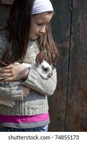 Sweet little girl hugs baby rabbit in the farm