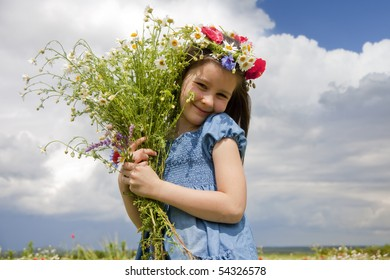 Sweet little girl on the field with summer flowers- poppies and daisies