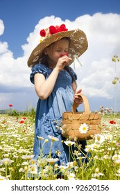 Sweet little girl on the wild field with blossom flowers.