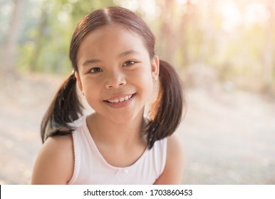 sweet little girl outdoors in the wind. portrait of attractive little student girl with beautiful. happy smiling child looking at camera - close-up, outdoors. jolly nature childhood leisure concept.