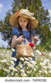 Sweet little girl pick a flowers in a wild meadow with poppies and daisies,