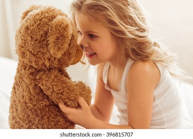 Sweet little girl is playing with a teddy bear and smiling while sitting on her bed at home