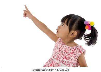 sweet little girl pointing at something, isolated on white background