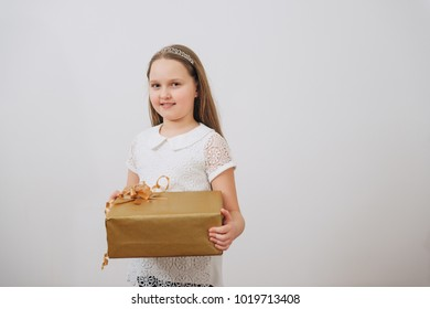 Sweet little girl with present box as a gift for birthday on white background.Daughter holding gift box for her mother.Mother`s day.