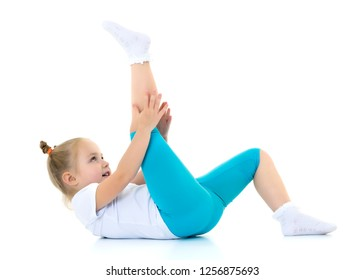 A sweet little girl shows gymnastic exercises that she learned at a sports school. The concept of sport and fitness. Isolated on white background.