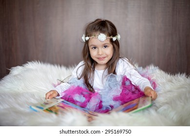 Sweet little girl, sitting in big chair with white fur, reading a book, wearing tutu skirt and headband