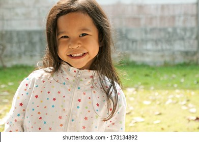 sweet little girl smiling outdoors