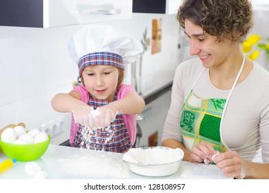 Sweet little girl sprinkle flour in kitchen