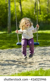 sweet little girl of two and a half years with blonde curly hair has a lot of fun an a swing on a garden playground.