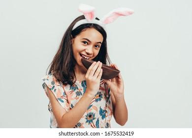 Sweet little girl wearing bunny ears eating chocolate Easter egg. Easter in Brazil