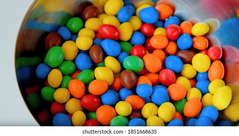 Sweet little glazed multicolored chocolate candies, m and m's in a silver iron bowl