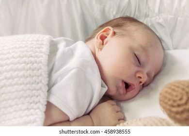 Sweet Little Newborn Baby Boy Sleeping On The Blanket With His Monkey Toy